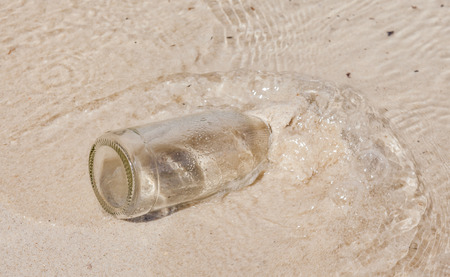sinks: The glass bottle sinks into water and beach sand
