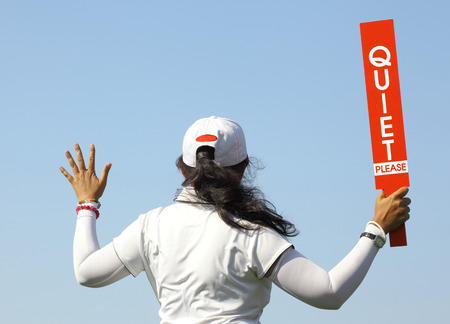 The lady volunteer shows the quite please sign before starting game in golf tournament.