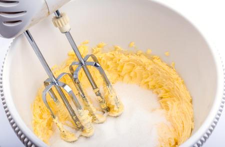 自家製グランジ自動ハンド ミキサーと卵、砂糖、バターの原料を焼きます。 写真素材