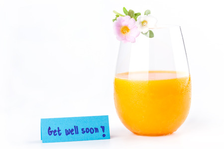 take a note: Fresh orange juice, pink and white rosemoss flowers and get well soon note on white background, concept of take care.