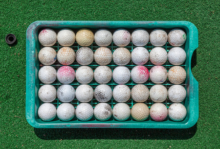 multiple objects: Roll of grunge golf balls in tray on green