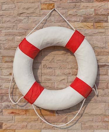 El blanco y rojo salvavidas que cuelga en la pared de ladrillo alrededor de la piscina, para la seguridad y rescate.