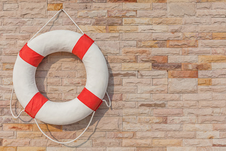 safety buoy: The life buoy is hanged on brick wall background nearby the swimming pool, for safety and rescue.