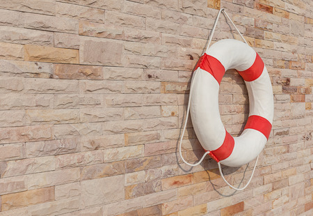 cinturon seguridad: The white and red life buoy is hanging on the brick wall around the swimming pool, for safety and rescue. Foto de archivo