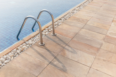 pool bars: Grab bars ladder in the clear blue swimming pool.