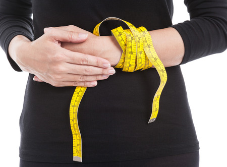 losing control: The woman in black with yellow measuring tape on her hand, healthcare and weight loss concept.