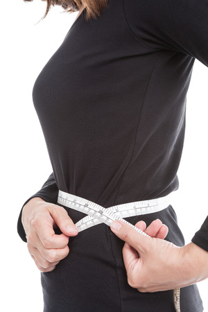 circumference: The woman in black measures her waist circumference with measuring tape on white background.