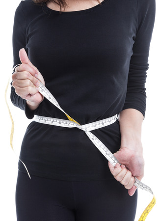 midriff: Diet and overweight concept, the woman in black try to reduce her weight with measuring tape on white background. Stock Photo
