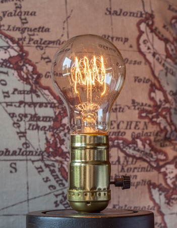 looping: Classic edison light bulb with looping carbon filament on map background. Stock Photo