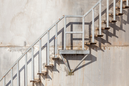 step ladder: The stairway on exterior of refinery industrial storage tank.