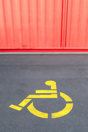 wheel chair: Disability priority sign for wheelchair using on concrete steet and corrugated painted wall.