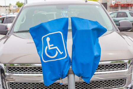 disabled parking sign: Reserved disabled parking sign on blue cover and stand. Stock Photo