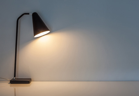 a study: The modern desk lamp illuminate on the wall background. (left the space for text)