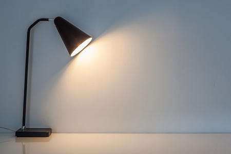 The modern desk lamp illuminate on the wall background. (left the right space for text) Stock Photo