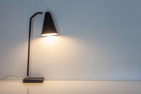 computer table: The modern desk lamp illuminate on the wall background. (left the right space for text) Stock Photo