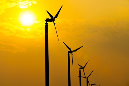 wind mills: The wind turbines silhouette generating electricity in the sunset sky. Stock Photo