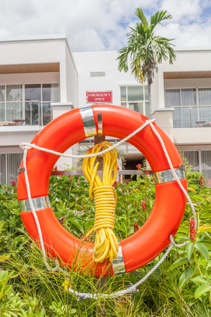 safety buoy: The orange life buoy with rope knot is hanging nearby the hotel swimming pool, for safety and rescue.