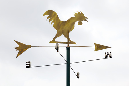 weathervane: The golden metal weathervane over the white sky background.