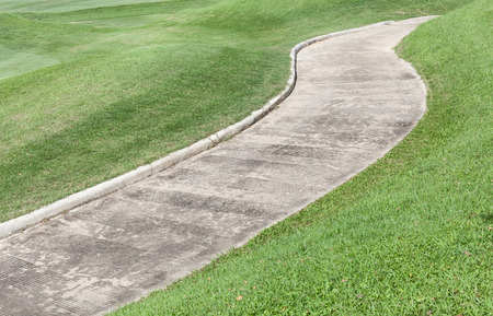 curving: Path curving through green lawn in golf course. Stock Photo