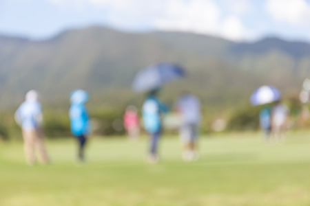 beholder: Blurred photo of golfer in green golf course. Stock Photo