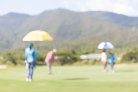 beholder: Blurred photo of golfer and caddy in green golf course.