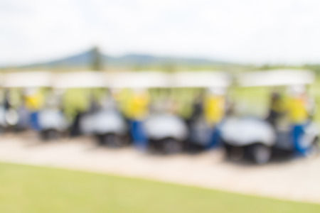 caddie: Blurred photo of row golf cart and caddy in golf course waiting for golfers.