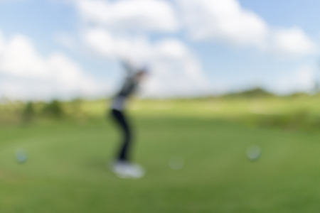 beholder: Blurred photo of golf player on green with beautiful nature scene. Stock Photo