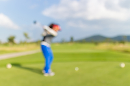 beholder: Blurred photo of woman golf player on green during golf match. Stock Photo