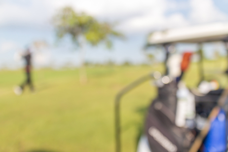 beholder: Blurred photo of golfer and golf cart in green golf course.