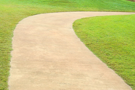 curving: Path curving through green grass in golf course. Stock Photo