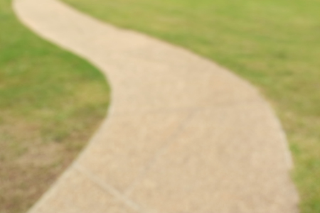 curving: Blurred photo of pathway curving through green lawn in golf course.