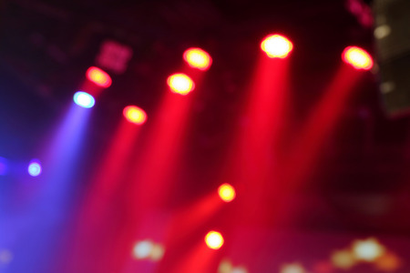 background design: Blurred photo of stage lights in live concert hall. Stock Photo