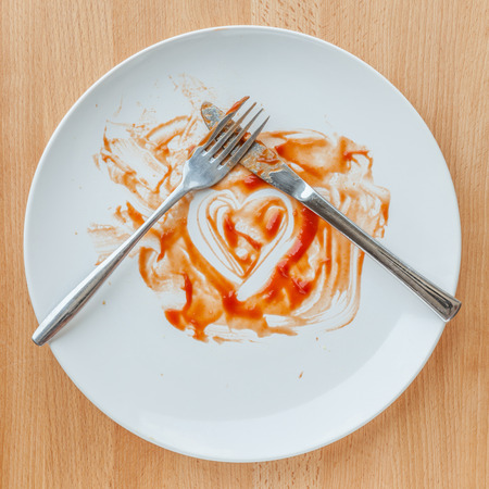 Knife and fork crossed in finish plate and heart shape ketchup, concept of tasty.