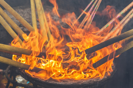 joss: Lighting up the joss stick with fire flames. Asian traditional religion for the Good luck. Stock Photo