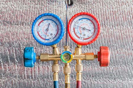 compression tank: Pressure gauges for auto air conditioner recharge. Stock Photo