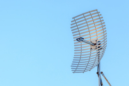 dipole: Microwave antenna dish on clear blue sky background.