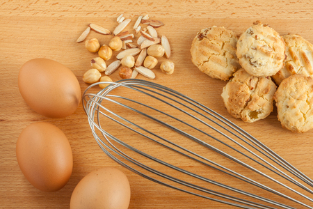 Tasty homemade cookies with fresh eggs ingredients, mixed nut and metal whisk beater.