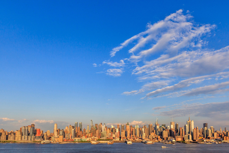 Panorama view of New York City skyline midtown Manhattan in colorful sunset and clear blue sky.