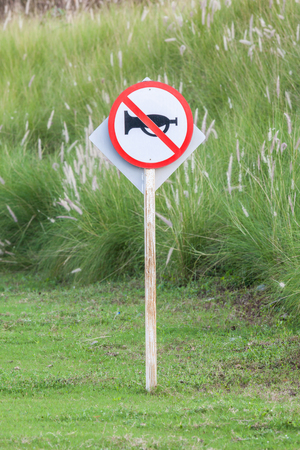 disturbing: The warning sign do not use vehicle horn with flowering grass background of green golf course objective for do not disturbing golf players.