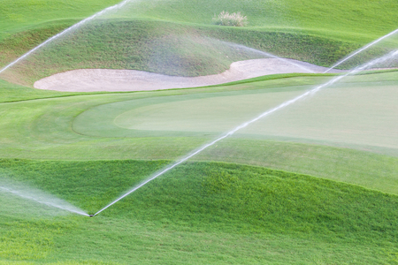 Sistema de riego de rociadores trabajando en fairway y búnker de arena de campo de golf verde. Foto de archivo