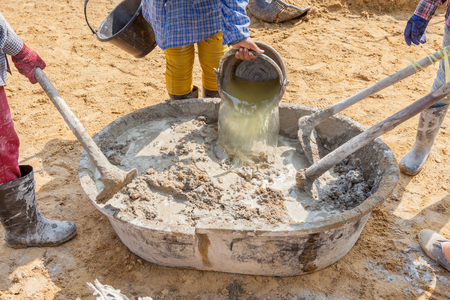 Concrete mixing step of sand, cement and water by construction workers pouring water to grunge cement tray at outdoor site.