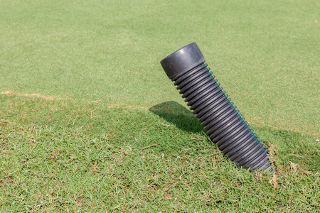 plastic conduit: The black plastic pipe tip under the meadow in green golf course for water draining., construction & infrastructure spare part.