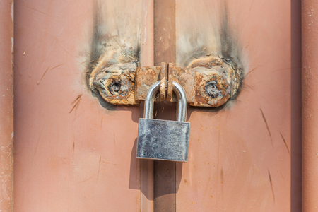 Contrasting of new metal padlock with old rusty metal entrance doors, security and private zone.