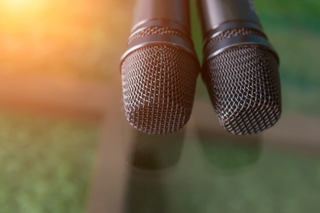 Close-up two microphone heads with warm fall color and blurred focus in background.