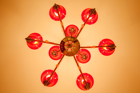 electric fixture: Looking up at the red chandelier with 6 lamps inside decorated on ceiling illuminate warm light room. Stock Photo