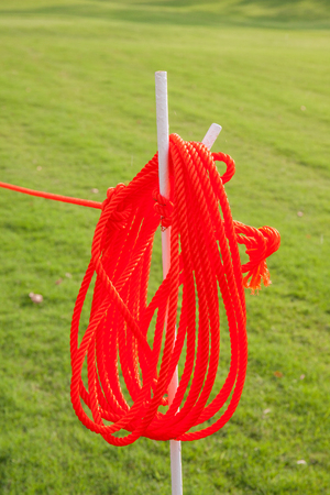 Red rope hanging on white wooden stick in green grass background.