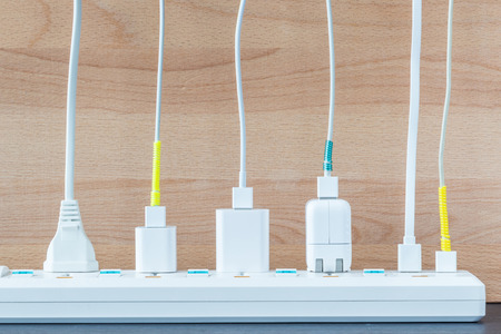 Variety electricity cables from charging station with wooden background, energy supply concept.