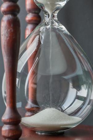 背景をぼかし、時間の概念を持つヴィンテージの木製砂時計で落ちた白い砂結晶。 写真素材