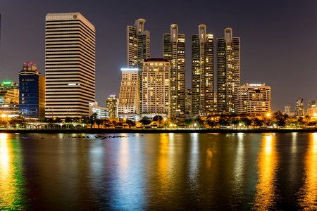 estate: Bangkok, Thailand- May 1, 2017. Benjakitti public park in Bangkok city in the twilight with skyscrapers and lights reflecting in the lake.