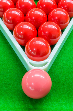 Red snooker balls set in triangle frame and one pink ball on top placed on green table.
